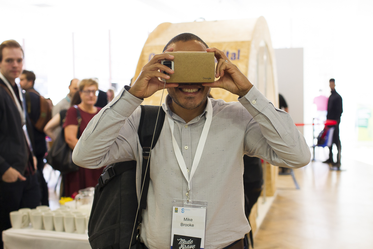 man looks through Google cardboard virtual reality head set
